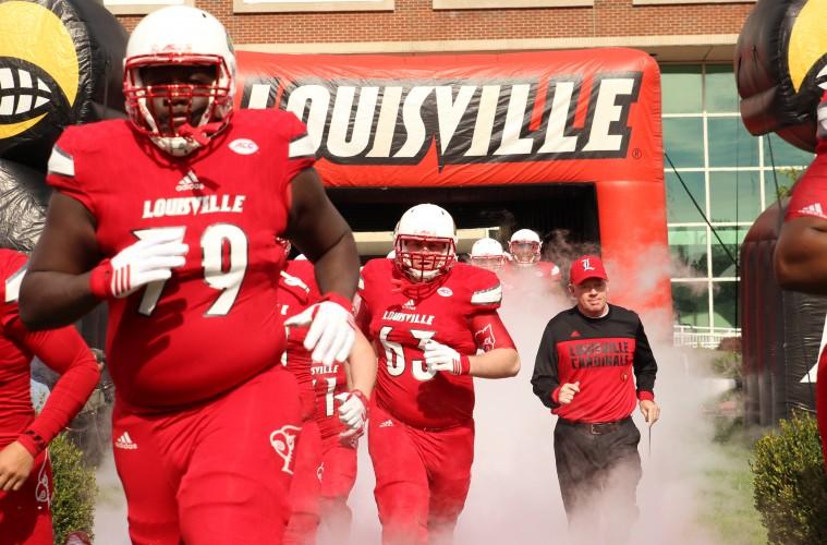 Kenny Thomas, Nathan Scheler, Bobby Petrino Entrance Louisville vs. Syracuse 11-7-2015 Photo by William Caudill